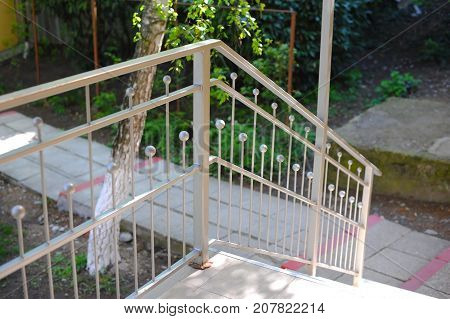 Metal railings near the stairs. Handrails are silver color