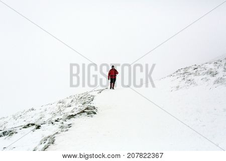 Brecon, Wales, UK: February 02, 2015: A man in a red jacket walks down the snow covered mountain path towards the camera on Pen y Fan. It is very dangerous climbing conditions with poor visibility and slippery footpaths