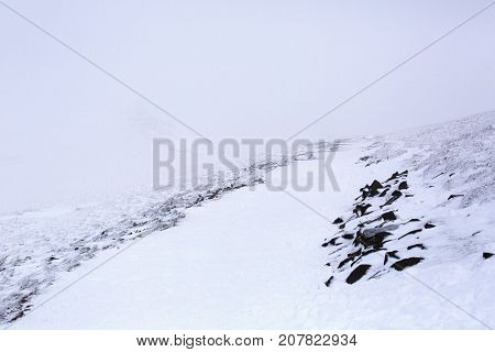 Snow covered mountain landscape of Pen y Fan Mountain in the Brecon Beacons National Park, Wales, UK with poor visibility and dangerous climbing conditions.