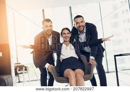 Two men in strict business suits roll their office co-worker in an office chair, also dressed in a business suit. They are having fun