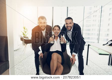 Two men in strict business suits roll their office co-worker in an office chair, also dressed in a business suit. They are having fun. She took off her shoes. She is scared