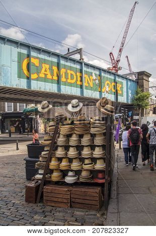 London, UK: July 26, 2016: Tourists walk past the colorful and funky shops on the main street in Camden Lock Market. Camden Town district of Inner London, one of the most popular places in London with tourists.