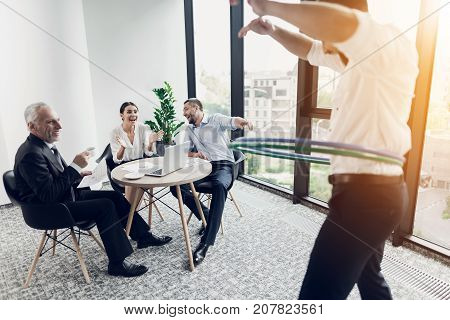 Three businessmen sit at the table and look at their colleague, who turns hula hoops. They are fun and they all laugh