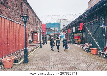 Traveler walking with happinest into the historic Red Brick Warehouses with snow in winter season at Hakodate Hokkaido Japan
