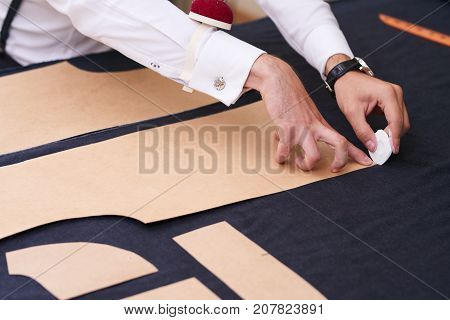 Closeup of tailors table with male hands tracing fabric making pattern for clothes in traditional atelier studio