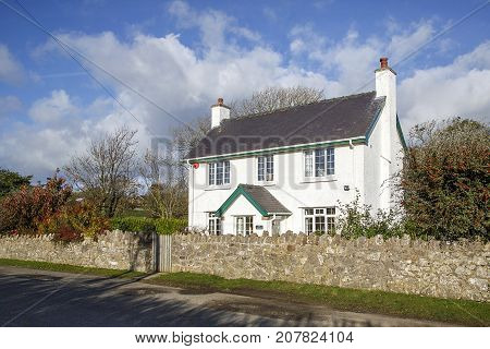 Gower, Wales, UK: November 10, 2016: A white detached cottage set in a rural country lane on the Gower peninsular with a front stoop and surrounding stone wall a with garden gate.