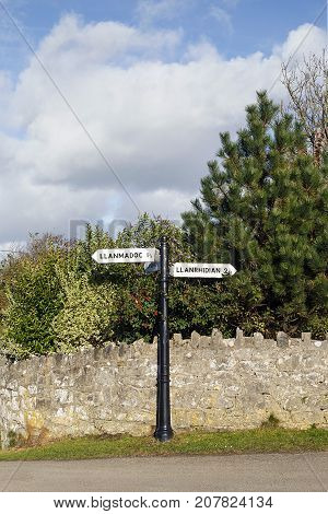 Country Signpost in rural Wales giving directions and mileage to the next village