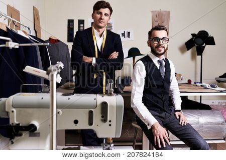 Portrait of two  handsome young tailors posing, looking at camera in traditional atelier studio behind sewing machines