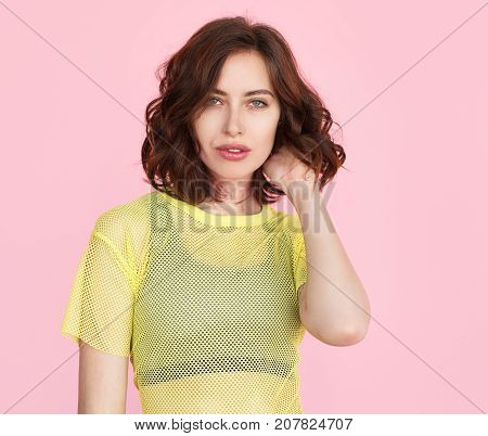 Young brunette in teenage clothing posing on pink looking confidently at camera.