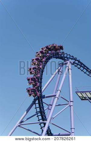 a loop of rollercoasters on the background of the sky with flipped over violet trolleys with people