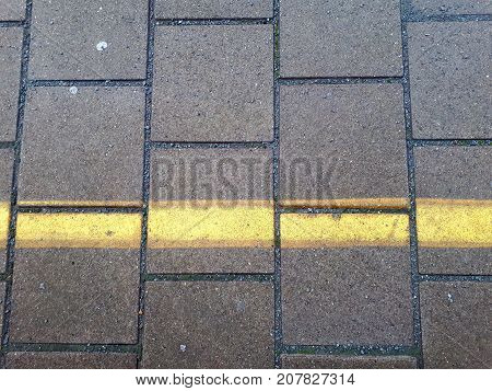 ground of a platform of a train station with square cobbles and yellow warning line