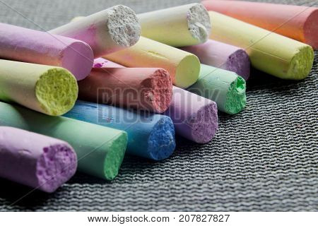 multi-colored chalk on a gray background close-up. side view