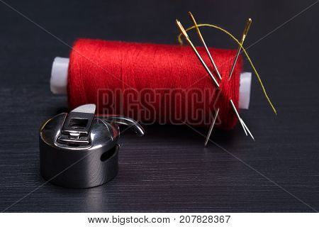 red skein of thread at the needle and the Shuttle hook for sewing machine on a dark background
