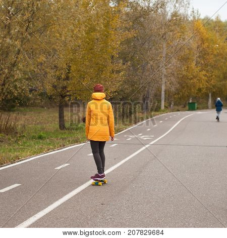 Unknowable girl riding longbone in the Park, the road in the autumn forest