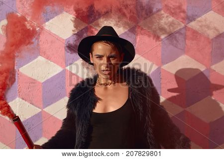 Trendy hipster girl in stylisih clothing posing provocatively with colored smoke bomb looking at camera.