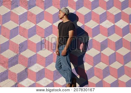 Side view of youngster in stylish clothing standing confidently on street painted wall in bright sunlight.