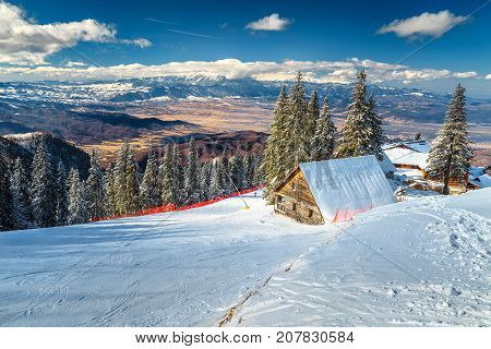 Fantastic winter landscape wooden chalets and stunning ski slopes in the Carpathians Poiana Brasov ski resort Transylvania Romania Europe