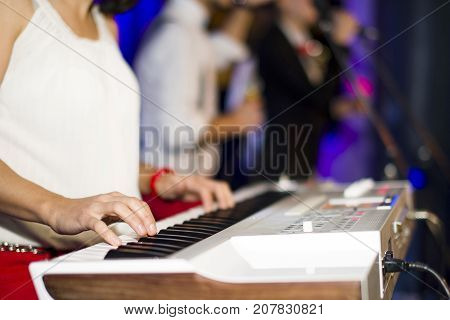 A female musician plays a concert synthesizer