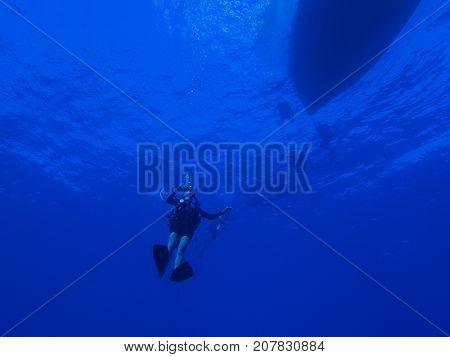 Diver Descending into the Blue Ocean with Boat Silhouette at Surface of Water