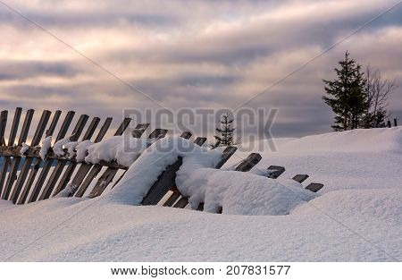 Fallen Wooden Fence On Snowy Hillside