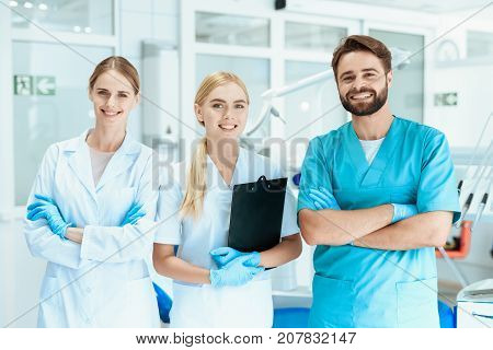 A dentist and two nurses are posing in the dental office on the background of dental equipment.