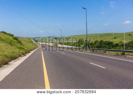Scenic road vehicle entry ramp onto highway travel route landscape.