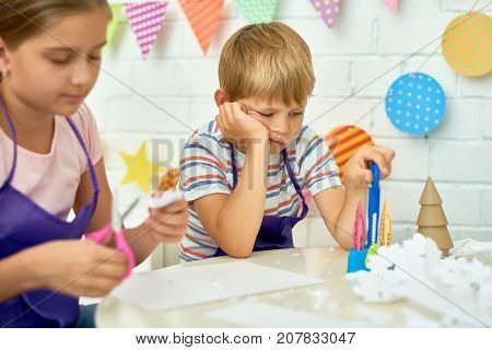 Portrait of sad little boy refusing to work in art and craft class of development school while other children making Christmas decorations