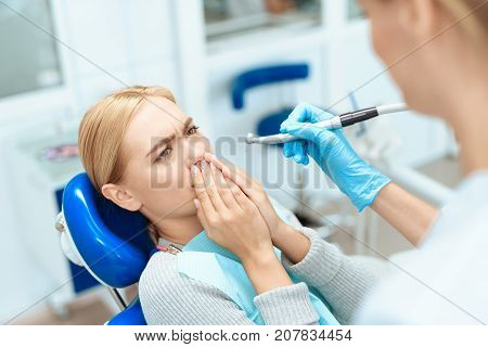 The woman came to see the dentist. She sits in the dental chair. The dentist bent over her. The woman is afraid