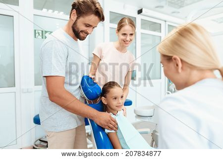 Roditli brought his daughter to the reception to the dentist. The doctor is standing next to the girl. Deochka sits in a blue dental chair
