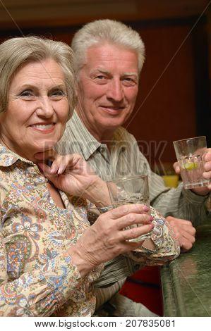 Senior couple drinking lemonade and looking at camera