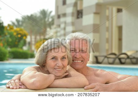 Senior couple relaxing at pool at hotel resort