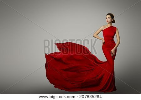 Fashion Model in Red Beauty Dress Sexy Woman posing evening Gown Flying Silk Tail over gray background