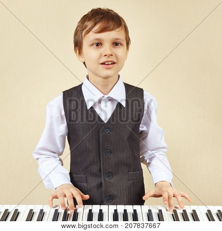 Young cut boy play the keys of the synthesizer