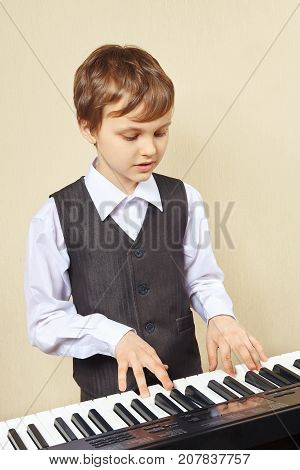 Little beginner pianist play the keys of the electronic synth