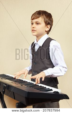 Young pianist in a suit playing the electronic synthesizer