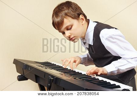 Young pianist in a suit playing the electronic organ