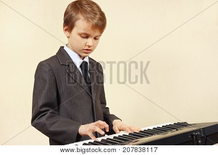 Little musician in a suit playing the electronic synthesizer