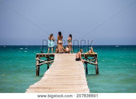 Alcudia, Majorca, Balearic islands, July 2017: Tourists enjoy Alcudia bay sea view from a wooden jetty