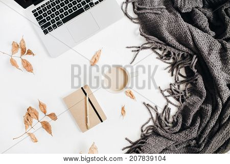 Office desktop with laptop craft diary golden pen terry plaid fall autumn leaves coffee with milk on white background. Flat lay top view.