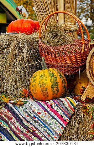 Pumpkin with wicker basket and rug on straw as autumn decoration at market place