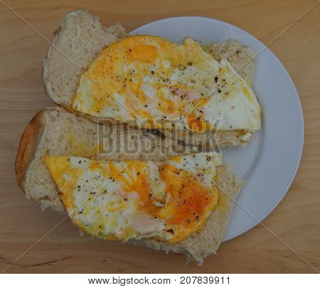 Simpel breakfast: Sandwiches with eggs, peper and salt on a white plate.