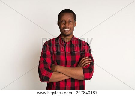 Stylish happy black man in red checkered shirt standing with cross arms portrait. White background in studio