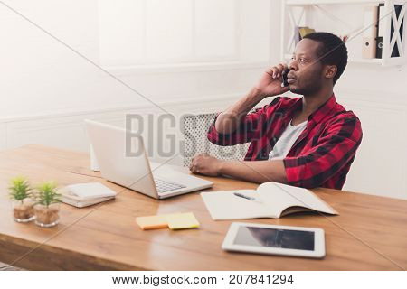 Important call. Young black businessman in casual has mobile phone talk in modern white office interior.