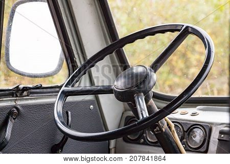 The steering wheel in the cockpit of an old car. Retro style