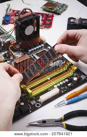 Technician plug in CPU microprocessor to motherboard. Computer upgrade in service center. Technology maintenance, electronics repair shop concept
