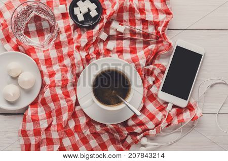 Coffee break at restaurant. Porcelain cup of black coffee, lump sugar and smartphone with earphones on checkered tablecloth at white wooden background, top view, copy space