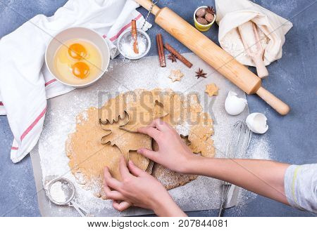 Preparing Christmas gingerbread cookies with cutter, dough and rolling pin - homemade festive Christmas bakery. Ingredients and utensils for bakery.