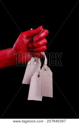 Painted in red color female hands make different shapes of fingers and hold white tag against on a black background. Close-up of hand.