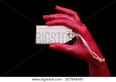 Painted in red color female hands make different shapes of fingers and hold white tag against on a black background. Close-up of hand. Halloween concept.