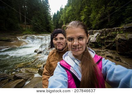 Mom and adult daughter sitting in the forest near the river and taking selfie. Happy senior woman and daughter taking selfie together. Holiday daughter with mother
